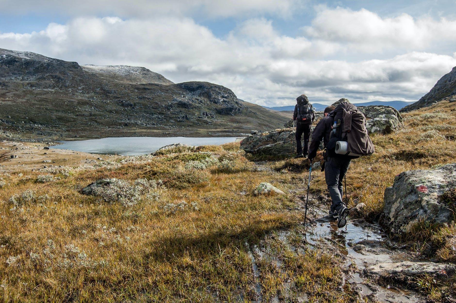 Dwoje ludzi wędrujących po górach obok jeziora