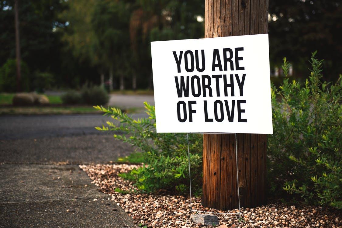 Jesteś Godzien Miłości Na Brązowym Drewnianym Słupku. Zdanie, które pomaga budować poczucie własnej wartości